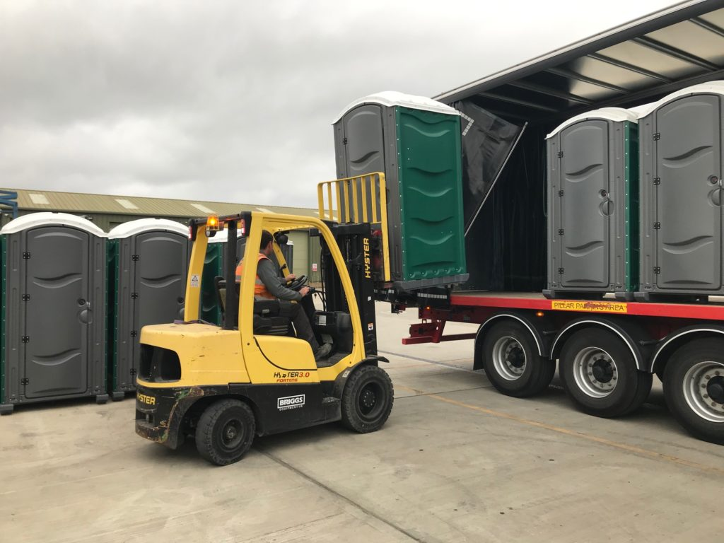 forklift unloading a portable chemical toilet